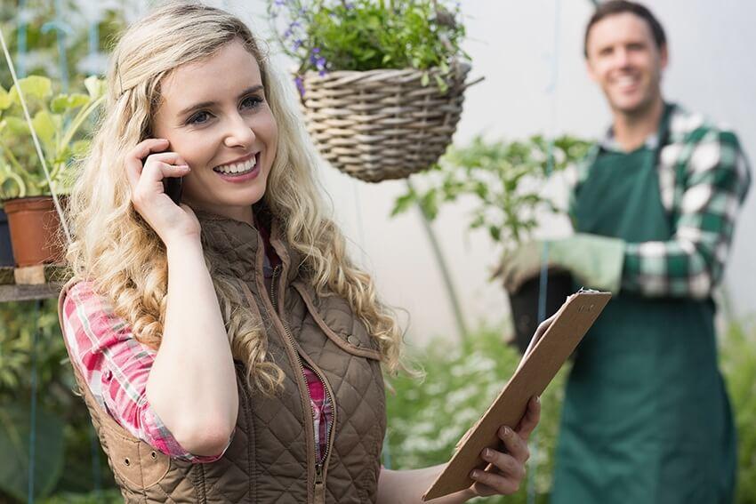 Landschaftsbauerin telefoniert mit einem Kunden