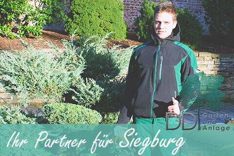 Garten und Landschaftsbauer steht in einem Garten in Siegburg, Schirfttzug Ihr Partner für Siegburg