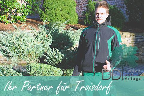 Garten und Landschaftsbauer steht in einem Garten in Troisdorf, Schirfttzug Ihr Partner für Troisdorf